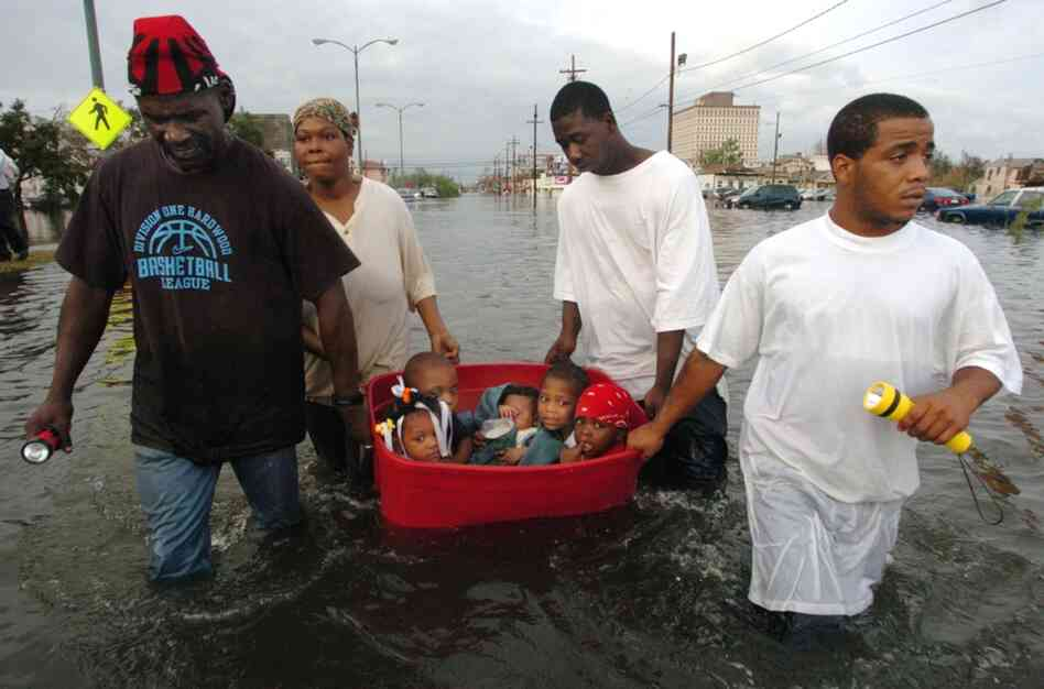 The flooding of New Orleans was well underway by Monday afternoon as John Rainey, John Rainey, Jr. and Courtney Davis helped Terry Fox tug a tub full of children to higher ground on South Broad Street on Aug. 29, 2005.