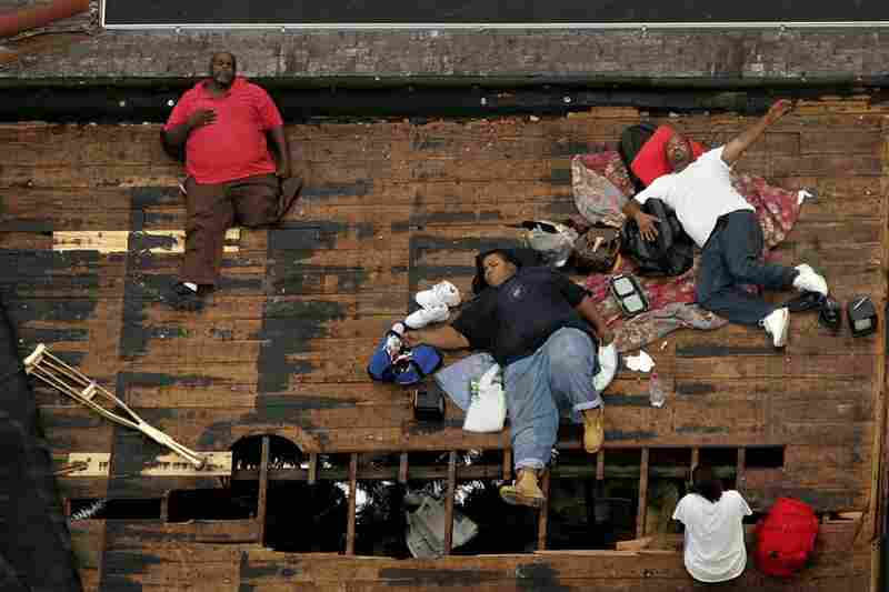 Residents, including a man with only one leg, wait on a rooftop to be rescued from the floodwaters of New Orleans on Sept. 1, 2005, as officials evacuate the city after Hurricane Katrina.