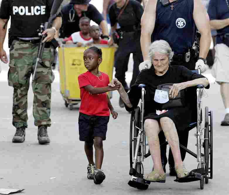 Tanisha Blevin, 5, holds the hand of fellow Hurricane Katrina victim Nita LaGarde, 105, as they are evacuated from Ernest N. Morial Convention Center on Sept. 3, 2005. Hundreds of people waited several days to be evacuated.
