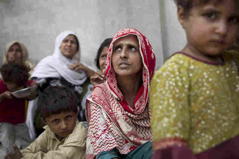 Bibi Gul (center) sits with her family in a school transformed into a camp for displaced people on the outskirts of Nowshera. The monsoon swallowed up Gul's house and two of her children. With no news of her son and daughter days later, she is distraught.