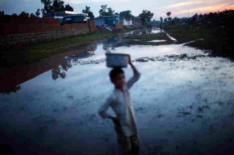 A boy makes his way along a flooded pathway in Pabbi.