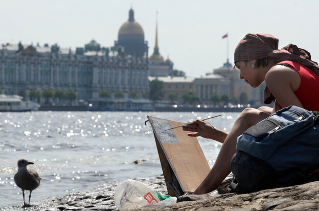 A Russian woman paints on banks of the Neva River.