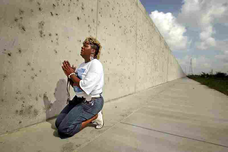 Oblique Weaver, who lost four family members during Katrina, kneels in the Lower 9th Ward at the repaired levee wall that was breached in the storm's aftermath. Weaver was attending the Great Flood memorial ceremony and march Aug. 29, 2006, one year after the storm.