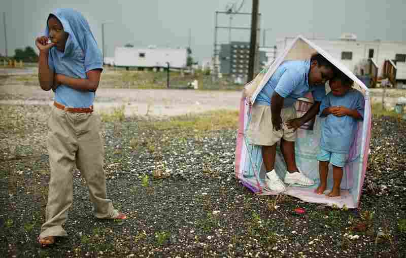 Children play in the rain at the FEMA Diamond travel trailer park May 22, 2008, in Port Sulphur, La.