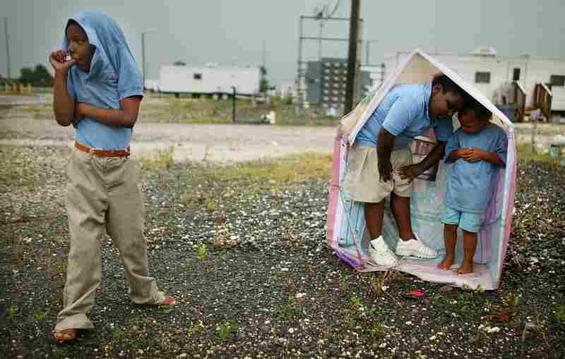 Children play in the rain at the FEMA Diamond travel trailer park May 22, 2008, in Port Sulphur, La.