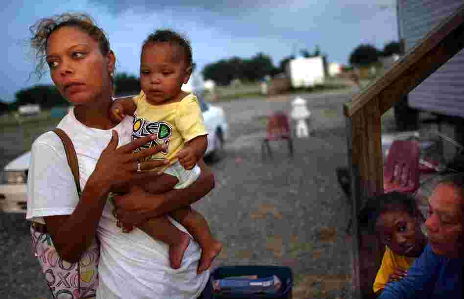 Shelly Phillips holds niece Kimmore Barthelemy in the FEMA Diamond travel trailer park May 26, 2008, in Port Sulphur, La. Phillips lost her home and job in Hurricane Katrina and is raising four children.