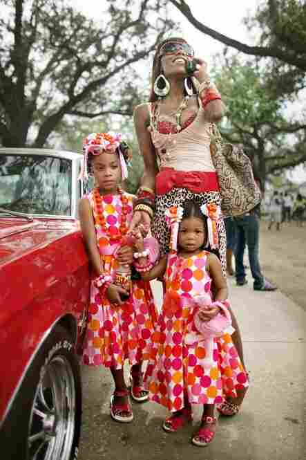 Angel Price talks on her mobile phone with her daughters Brielle, 8, and Cache, 2, as the Original Big 7 Social Aid and Pleasure Club holds a traditional second line parade May 14, 2006, in New Orleans' 7th Ward. It was first time the parade had been held since Hurricane Katrina.