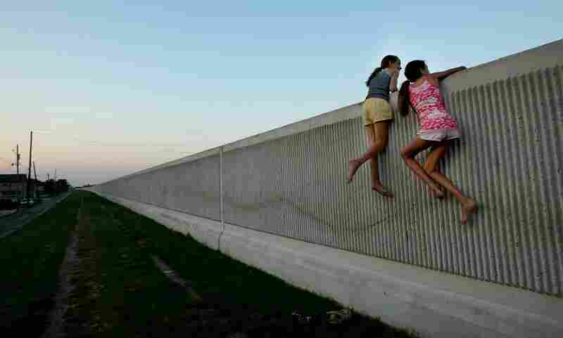 Isabella Lander (left) and Arabella Christiansen climb on the 17th Street Canal levee May 29, 2008, in Metairie, La. Despite $22 million in repairs, the 17th Street Canal levee, which broke during Hurricane Katrina, is leaking. Experts fear the levee could fail again in another large storm.