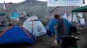 Lilian Ramirez sweeps outside a tent set up near the collapsed mine
