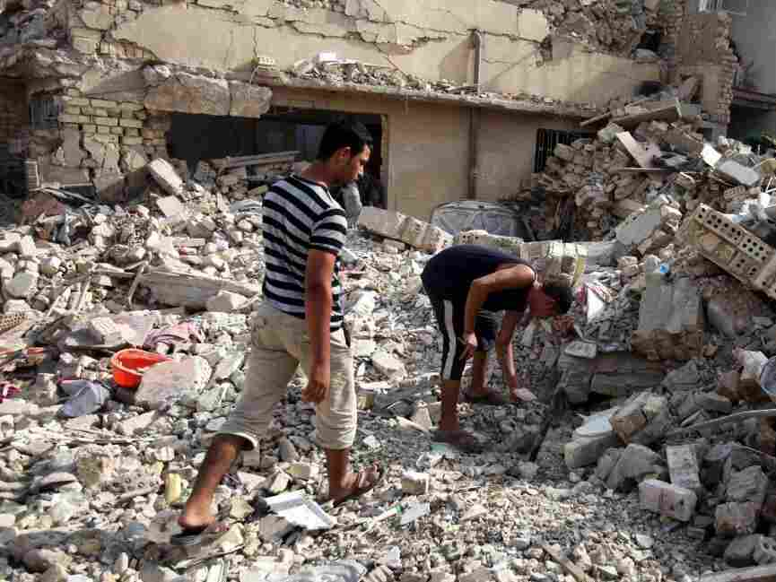 Iraqis survey a collapsed building in Baghdad the day after several bombings across Iraq.
