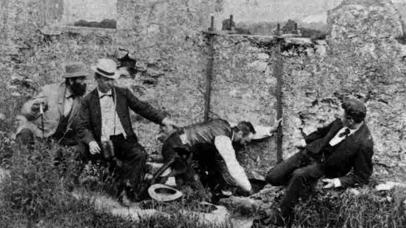 Group of men kiss the Blarney Stone in Ireland circa 1880