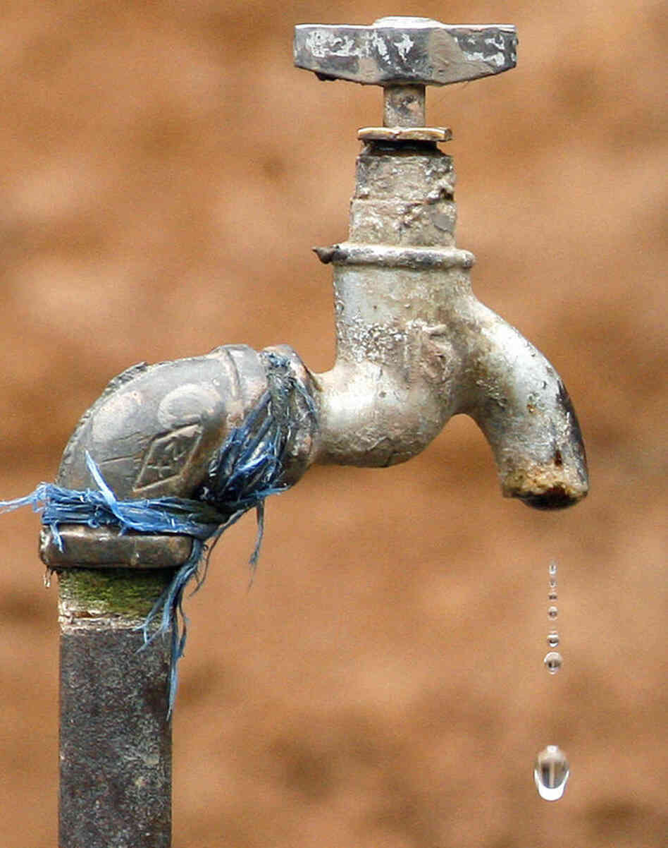A drop of water drips down from a tap.