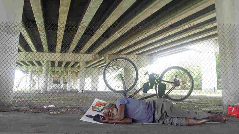 Ray McNair rests under I-95 in Overtown. Tom Ervin For NPR