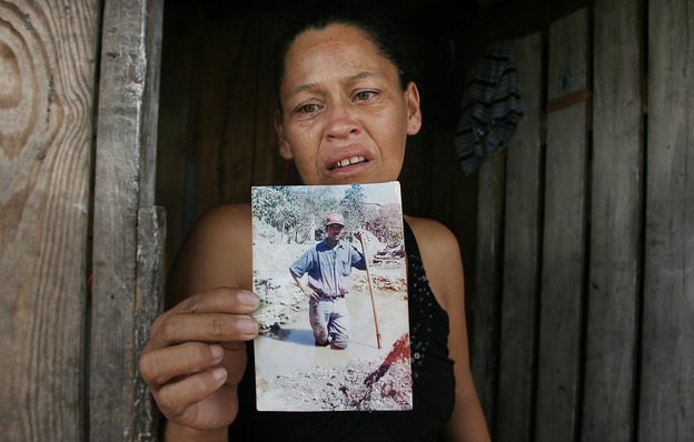 Marleni Xiomara Suarez Ortega weeps as she holds up a photo of her husband, Miguel Angel Carcamo, at her home in Tegucigalpa, Honduras. Her husband was allegedly among the 72 migrants found dead in northern Mexico this week.