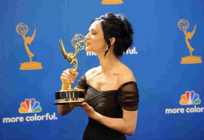 Actress Archie Panjabi, winner of the Outstanding Supporting Actress in a Drama Series Award for The Good Wife kisses her trophy.