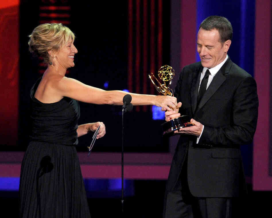 Actor Bryan Cranston, right, accepts the Outstanding Lead Actor in a Drama Series award for Breaking Bad from actress Edie Falco onstage at the Emmy Awards.