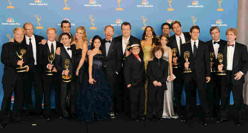 Cast and crew of Modern Family, winners of the Outstanding Comedy Series Award pose in the press room at the Emmy Awards.