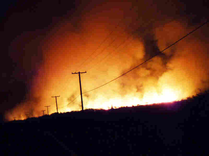 Fire lights up the smoke-filled sky in the early hours of May 4, along Honoapiilani Highway in Maui,