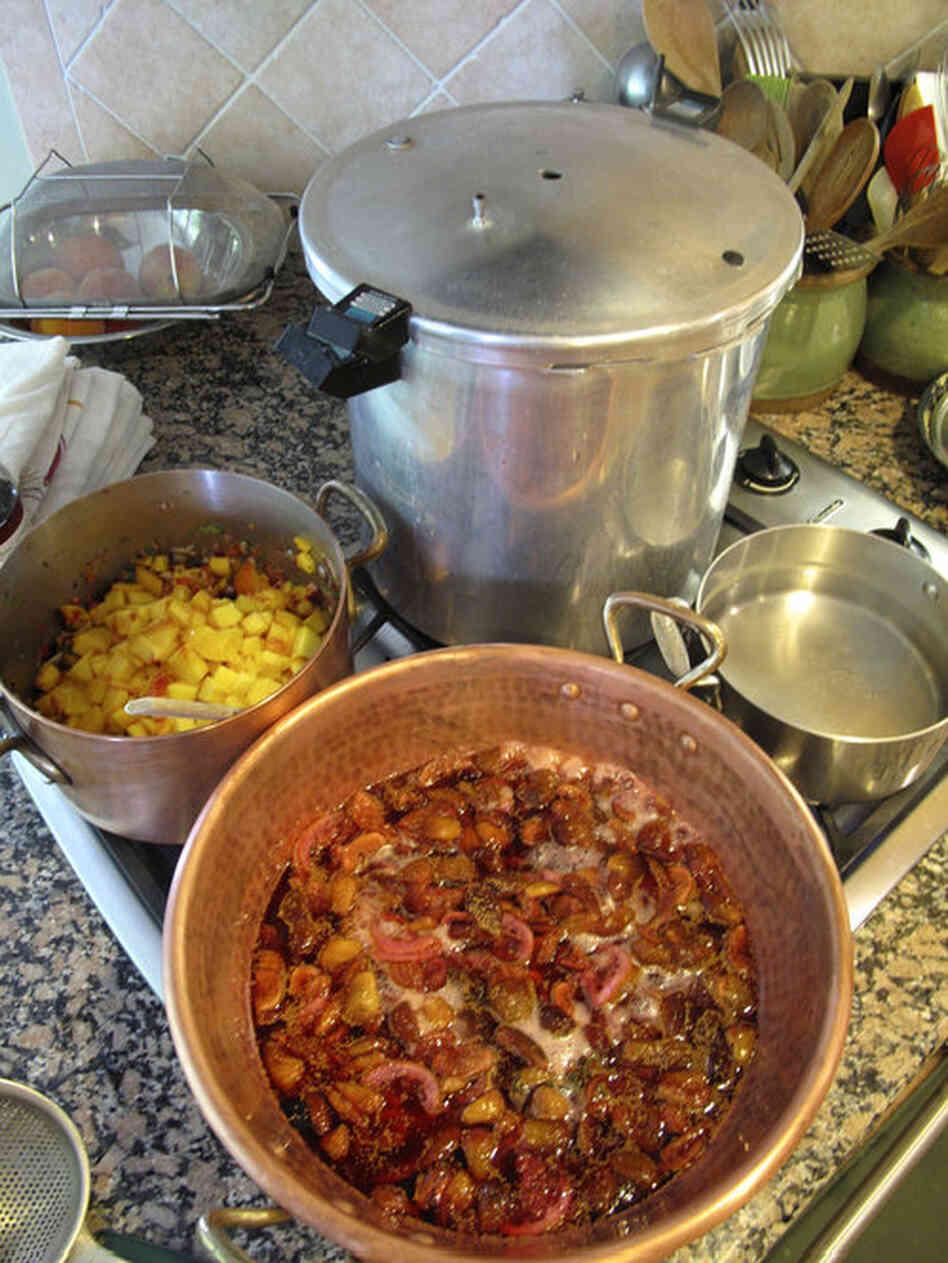 Peach salsa (center left) and fig confiture cook while the canner sits nearby, ready for sealing them in jars. Though Barrow uses a pressure canner for her home canning, she teaches her classes using the boiling water bath method.