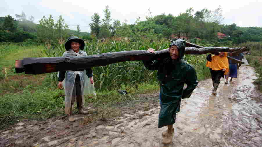 Villagers from Guangmenyan move roof beams and bamboo poles to take with them to their new homes.