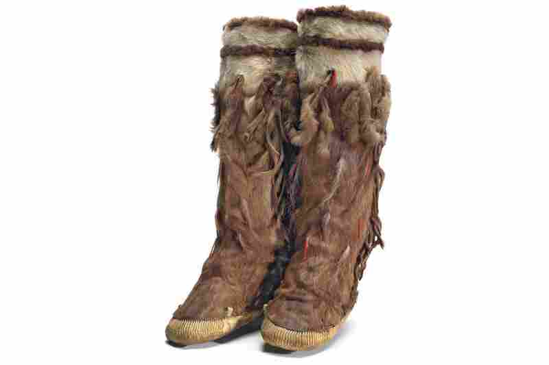 Yupik boots. A woman's tasseled winter boots made from caribou leg skins. The bands on top are white caribou belly with stripes of either beaver or bear. One pair of boots required all four of the animal's limbs.