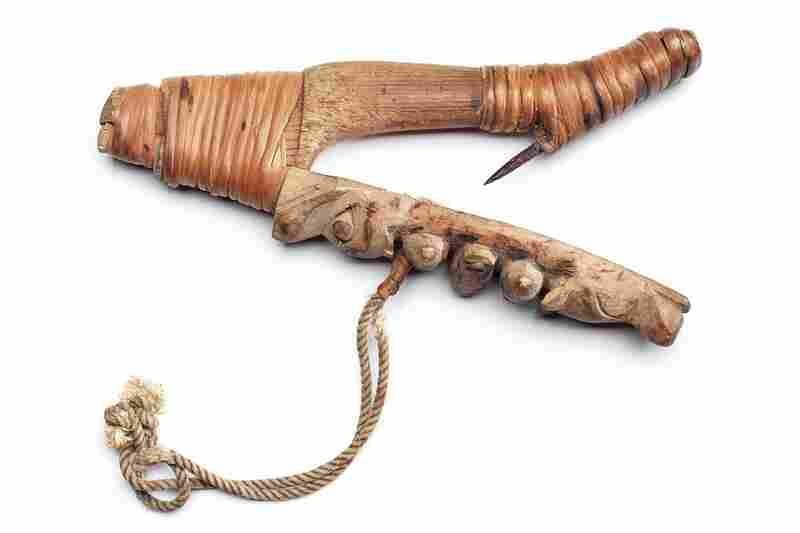 Sugpiaq halibut hook. Halibut was a staple food and was caught with these V-shaped wooden hooks, which were floated just above the seafloor by an inflated stomach buoy. Spirit figures were carved on the hook to attract the fish.