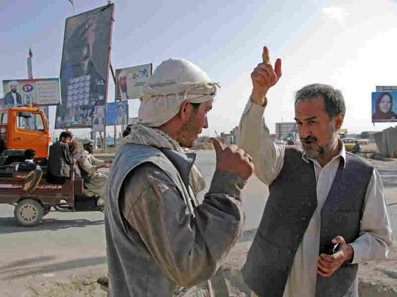 Candidate Daoud Sultanzoi speaks with a worker about where to place a sign