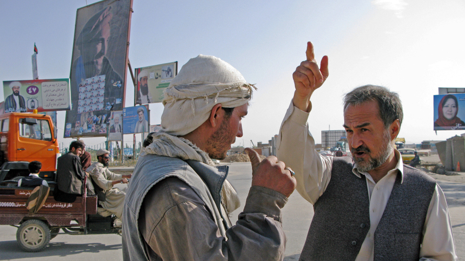 Incumbent Daoud Sultanzoi talks with a worker about where to place a campaign billboard. But being outside like this in Ghazni carries high risks. In recent weeks, two other parliamentary candidates were killed, one kidnapped and one injured. Other campaign billboards are in the background.