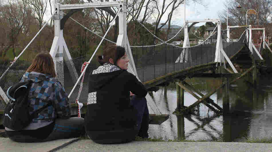 Two girls near a buckled foot bridge south of Christchurch, New Zealand.