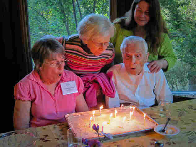 "Camp director Caitlin Morgan (upper right) says people with dementia often don't get the interaction they need. ""Just because someone gets a diagnosis of Alzheimer's or other dementia doesn't mean life is over,"" Morgan says. Campers (from left) Deborah Gallagher, Jeanne Vasconcelles and Jimmy Johnson celebrate their birthdays together after Saturday night's dinner."
