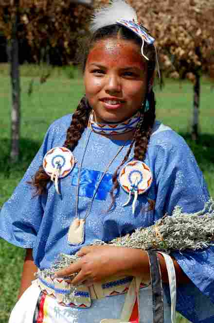 Brittany Poor Bear, 12, from Lake Andes, S.D., holds a bouquet of women's sage on the fourth day of the Isnati, when the girls are presented to the community at the womanhood ceremony.