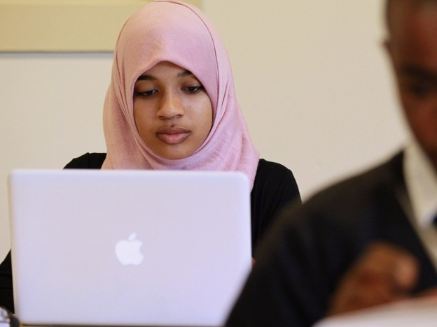 A young Muslim woman uses her computer. Faith-based search engines help Christians, Jews, and Muslims surf the Web according to their religious beliefs.