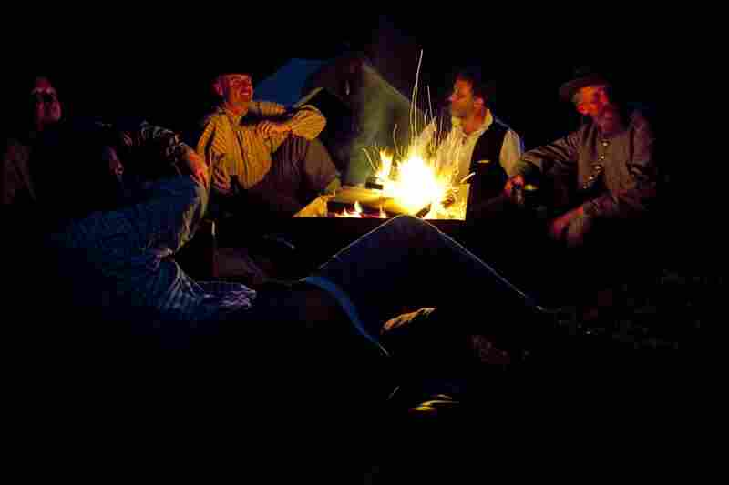 Members of the ACWS 18th Virginia Infantry sit around a fire at their part of the Confederate camp the night before a re-enactment for the public in Market Deeping, England.