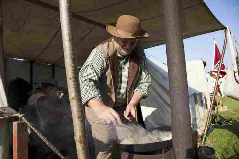 A Confederate re-enactor prepares a meal at a camp set up in the town of Hingham, England. Re-enactors came to Hingham for a festival honoring Abraham Lincoln, whose ancestor Samuel Lincoln immigrated to America from Hingham.
