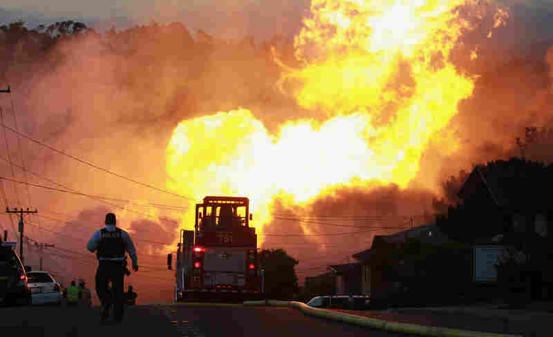 A law enforcement official runs towards a massive fire in a residential neighborhood.