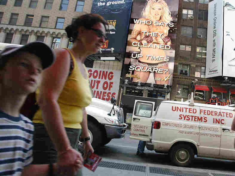 Child walks hand in hand with mother with porn billboard in background.