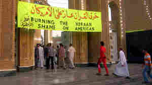 """A banner in English and Arabic that says """"Burning the Koran — Shame on American."""""""