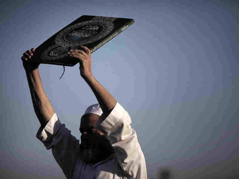 A Palestinian Muslim holds up a copy of the Quran.