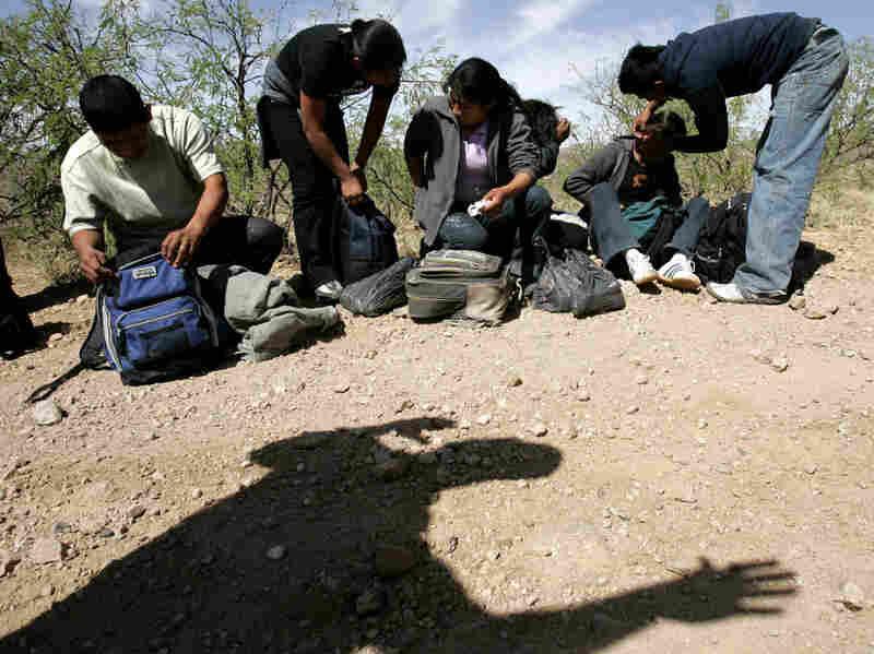 A U.S. Border Patrol agent casts a shadow below a group of migrants detained near Arivaca, Ariz.
