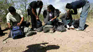 A U.S. Border Patrol agent casts a shadow below a group of migrants detained near Arivaca, Ariz.