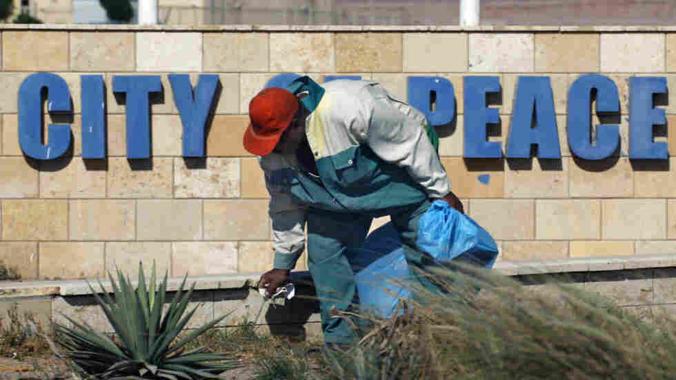 An Egyptian worker spruces up the area near a peace slogan at the Red Sea resort of Sharm el-Sheikh,