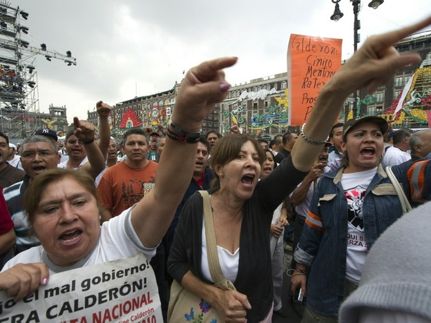 Protesters shout slogans against Mexican President Felipe Calderon in front of the National Congress where the president delivers his annual address in Mexico City,  Sept. 2. Recent opinion polls confirm that the majority of Mexicans feel that their country is worse now than it was when Calderon took over in 2006.