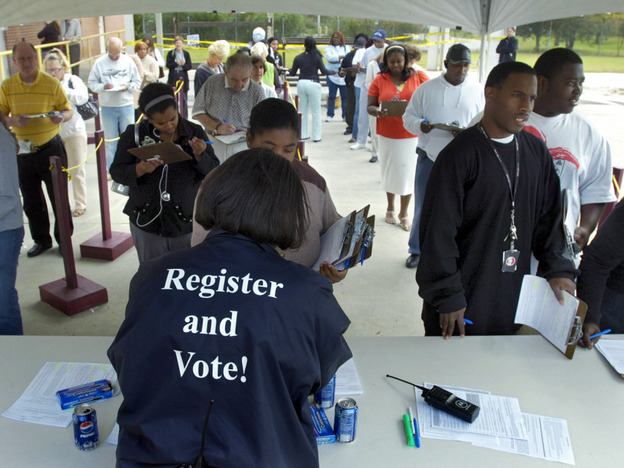 An election supervisor hands out absentee ballots during early voting in Savannah, Ga., in 2008. Federal officials dropped opposition to a Georgia law requiring that voters prove they are U.S. citizens.