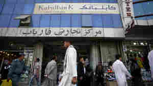 Afghans walk past a branch of Kabul Bank.