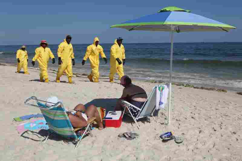 Workers who were cleaning beaches on the Florida coast pass by tourists.