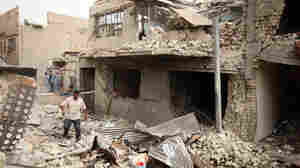 Iraqis inspect the scene of a car bomb attack in Baghdad's Kazimiyah neighborhood