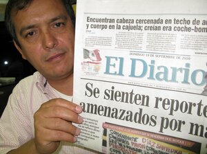El Diario editor Pedro Torres with the front page featuring the Mexican flag dripping blood.