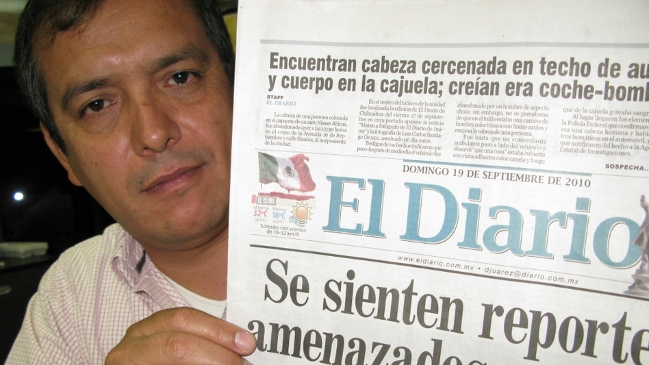 Pedro Torres, editor of <em>El Diario</em>, holds the front page featuring the Mexican flag dripping blood. Two of his journalists have been killed over the past two years.