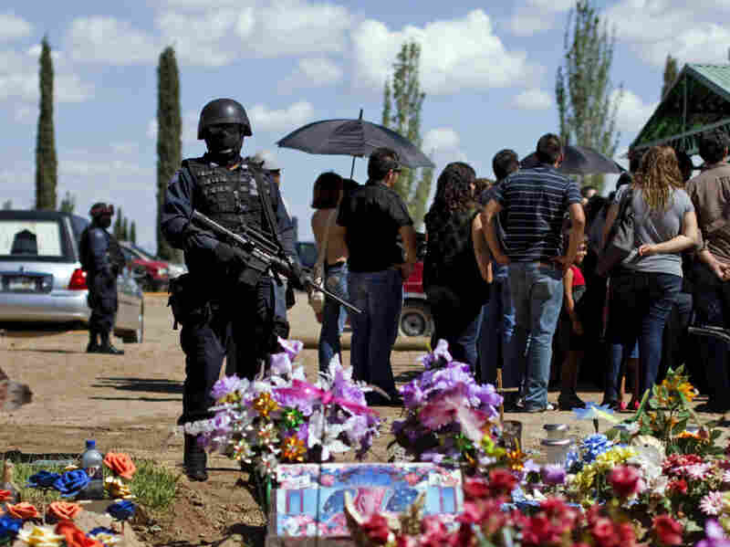 Federal police officers stand guard during the burial of newspaper photographer Luis Carlos Santiago.