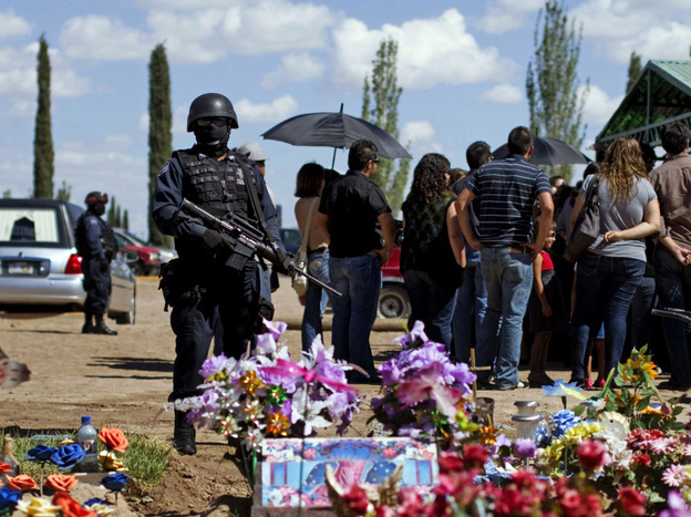 Federal police officers stand guard during the burial of <em>El Diario de Juarez</em> newspaper photographer Luis Carlos Santiago in Ciudad Juarez, Mexico, on Saturday. Santiago was shot and killed Sept. 16.